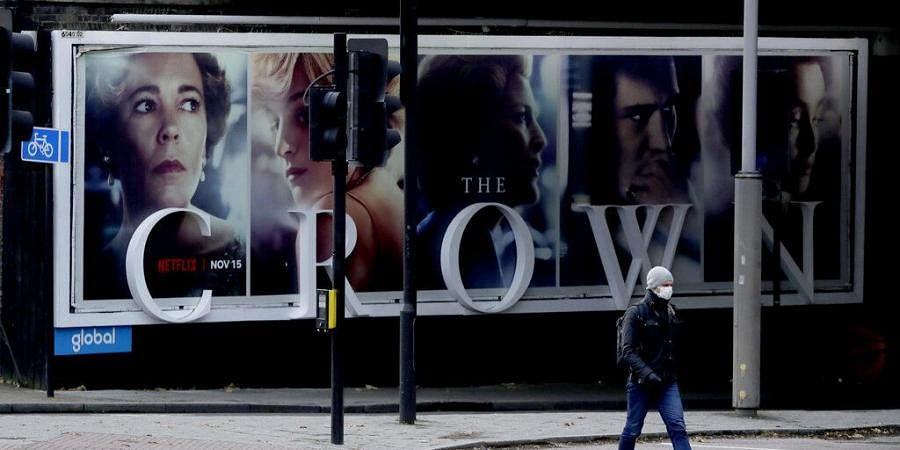 A man wearing a face mask walks past a billboard advertising 'The Crown' television series about Britain's Queen Elizabeth II and the royal family.