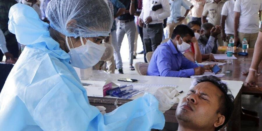 A health worker takes a nasal swab sample at a testing camp for COVID-19. (Photo | AP)