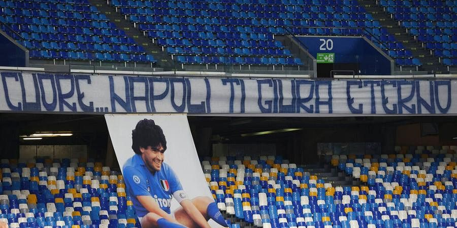 A giant image of Diego Maradona is displayed under a banner reading in Italian 'Here, Naples swears to you eternal love' in the stands