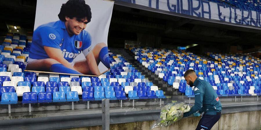 Napoli's Lorenzo Insigne lays a bouquet of flowers under a photo of Diego Armando Maradona at the San Paolo stadium