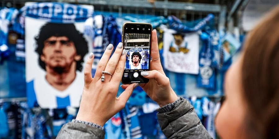A fan takes pictures of the memorabilia hanging on the gates of the San Paolo stadium in Naples, Italy