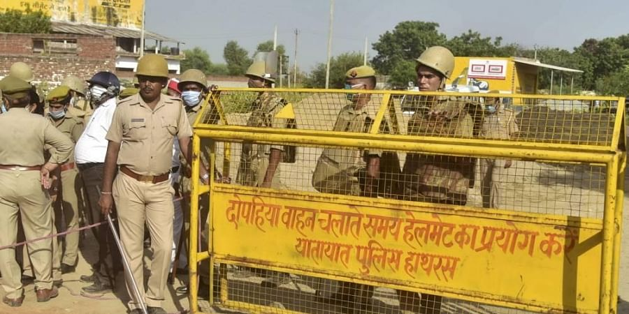 Police personnel stand guard near a barricade on a road leading to Bulgari village following the death of a 19-year-old Dalit woman after an alleged gangrape in Hathras district