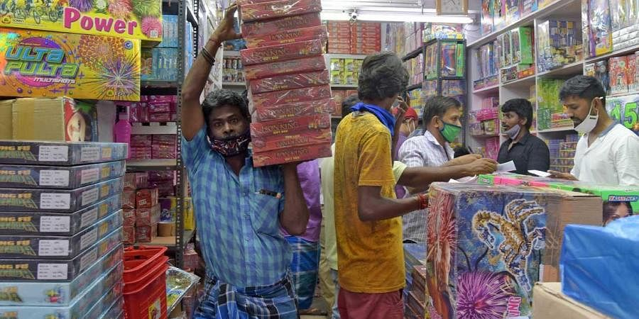 A man carries packets of firecrackers for display at a shop on the eve of Diwali in Chennai. (Photo | Martin Louis, EPS)