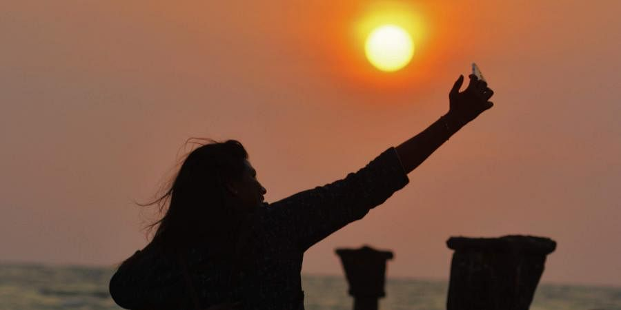 A woman takes a selfie against the backdrop of the setting sun.