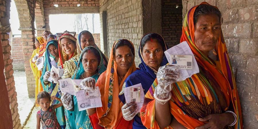 Voters display their identity cards as they stand in a queue to cast their votes during the third phase of Bihar Assembly Elections.