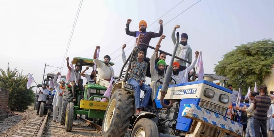 Farmers raise slogans as they block train tracks with tractors on the twentieth day of their ongoing 'Rail Roko' protest