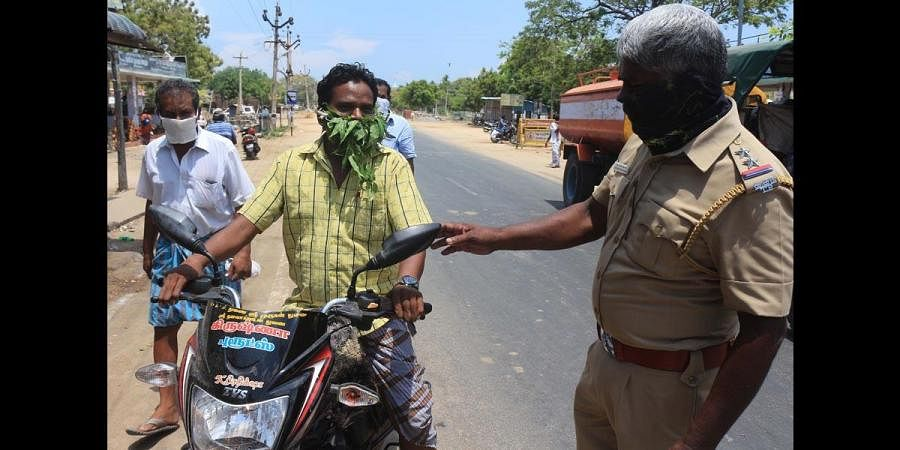 A file photo of a police personnel warning a man for wearing mask made of neem leaves while travelling on a two-wheeler. (Photo | EPS)