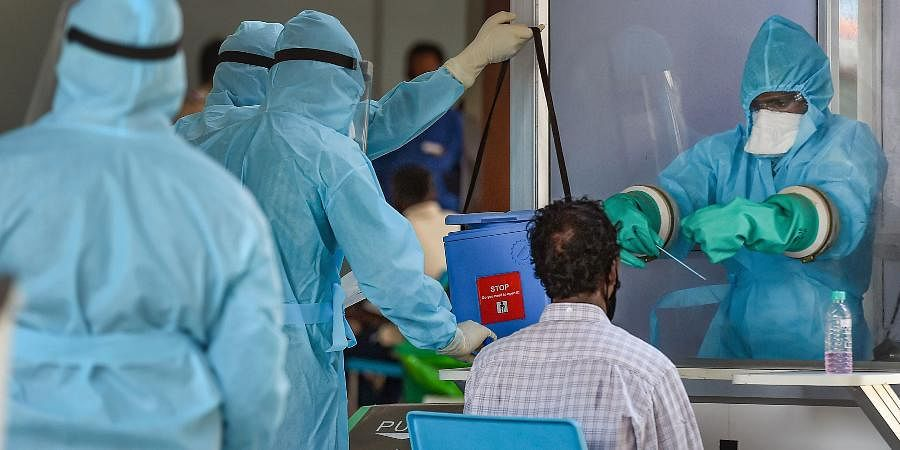 A medic takes samples from an Indian national arriving from Myanmar at Anna International Airport, during the ongoing COVID-19 nationwide lockdown, in Chennai.