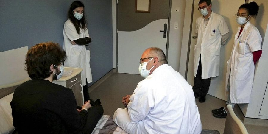 Psychiatrist Olivier Guillin, center, talks with Nathan, a 22-year-old student, at the Rouvray psychiatric hospital, in Rouen, western France, Wednesday, Nov. 25, 2020.