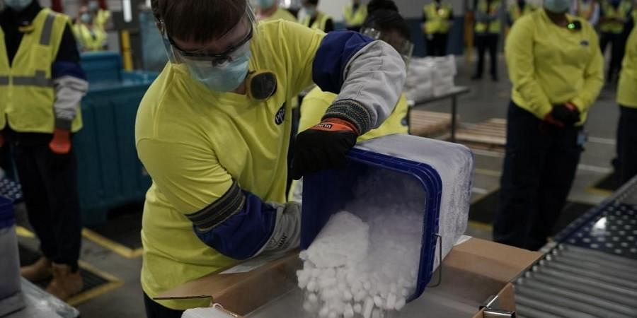 A worker pours dry ice into boxes containing the Pfizer-BioNTech Covid-19 vaccine. (Photo | AFP)