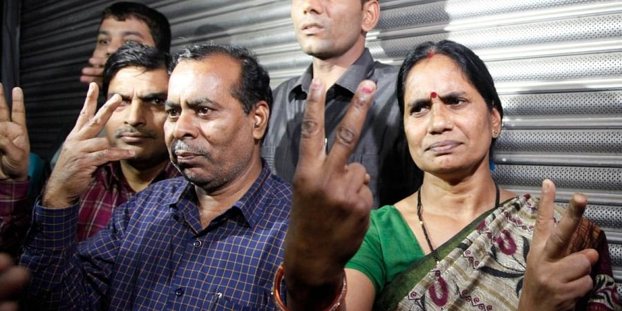 Nirbhaya's parents show victory sign after the hanging of their daughter's rapists in New Delhi on Friday