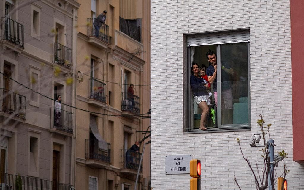 People stand in their balconies during a nationwide confinement to counter the coronavirus in Barcelona, Spain on March 29, 2020.