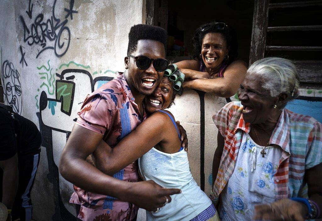 Cuban singer Cimafunk hugs a woman during a music conga through the streets of Cuba's Old Havana neighborhood during the 35th Havana International Jazz Festival on January 15, 2020.