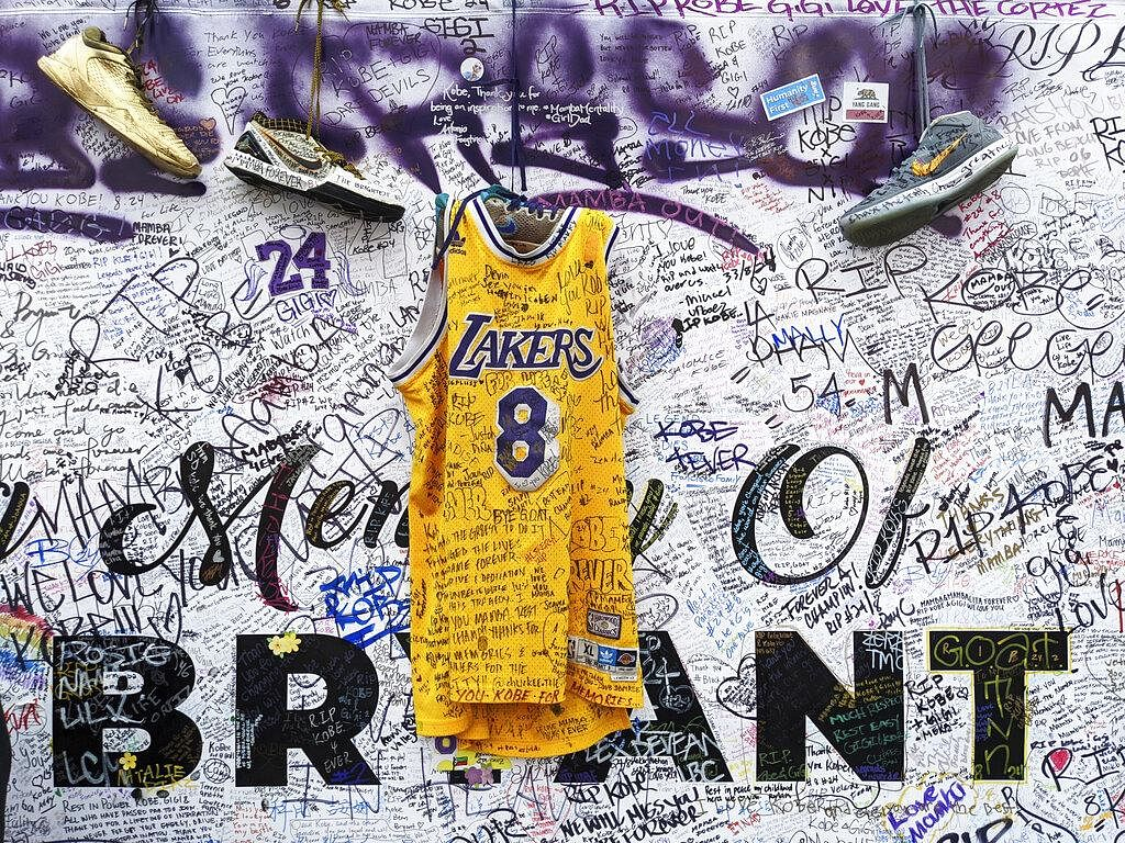 Sneakers and a Los Angeles Lakers jersey with the number 8 worn by NBA star Kobe Bryant hang at a memorial for Bryant in Los Angeles on February 2, 2020, a week after he was killed in a helicopter crash.