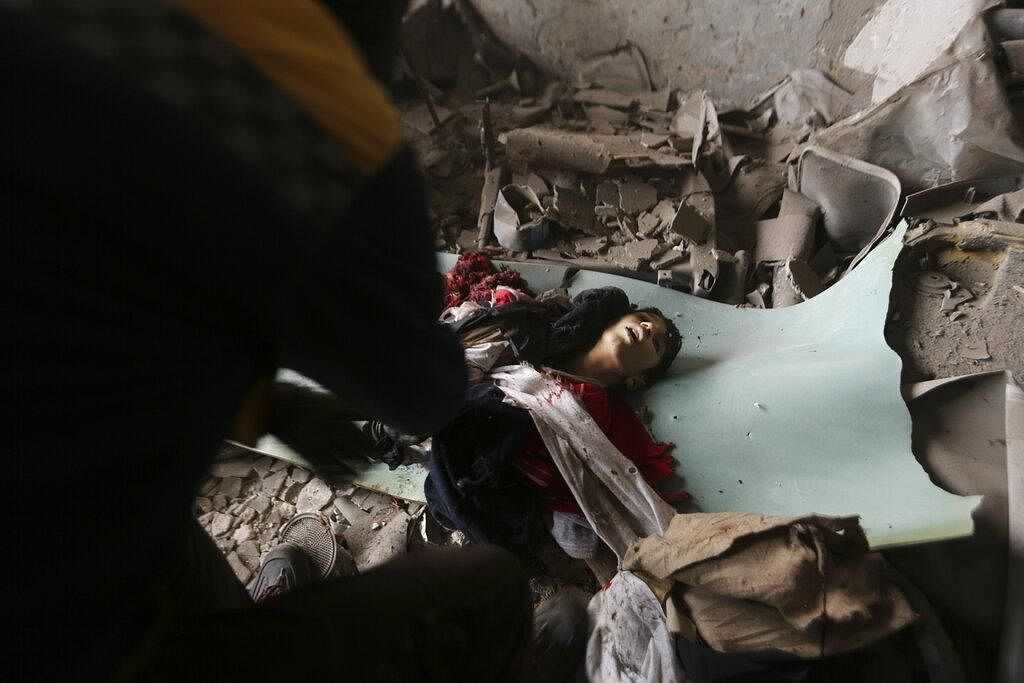 An emergency crew recovers the body of a boy killed in a government airstrike in the city of Idlib, Syria on February 11, 2020.