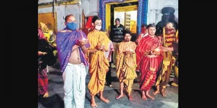 Servitors holding earthen lamps in front of Haribaldevjew temple on Tuesday