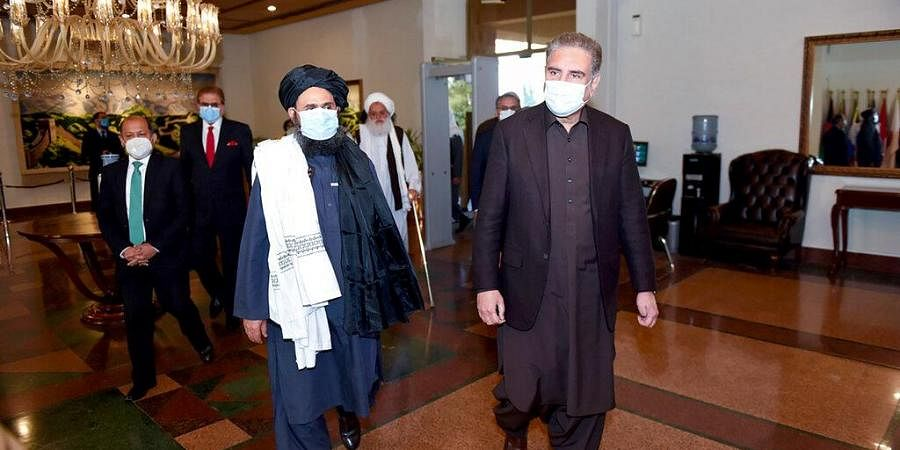 Pakistan Foreign Minister Shah Mahmood Qureshi, right, and Mullah Abdul Ghani Baradar, head of a Taliban political team, arrive at the Foreign Ministry.
