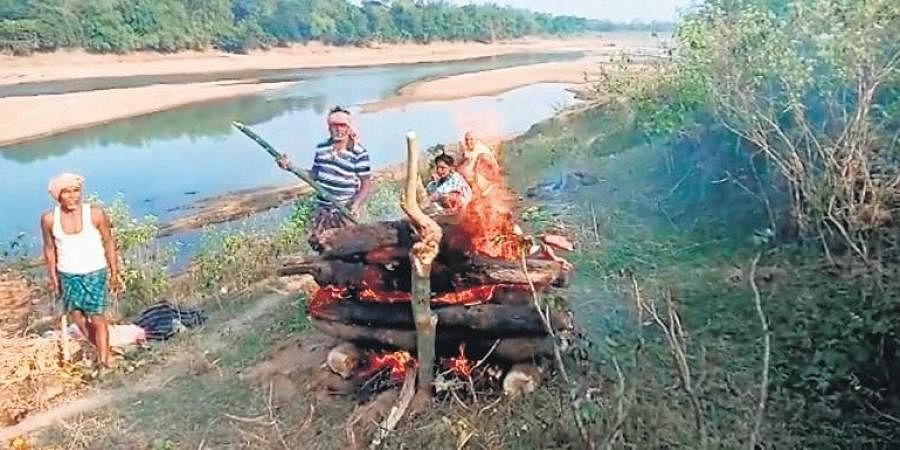 Mayadhara Naik  helping villagers cremate a body on the banks of a river in Udala