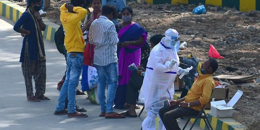 A health worker collects a swabsample for Covid test from a KSRTC passengerin Bengaluru on Tuesday. (Photo| Shriram BN, EPS)
