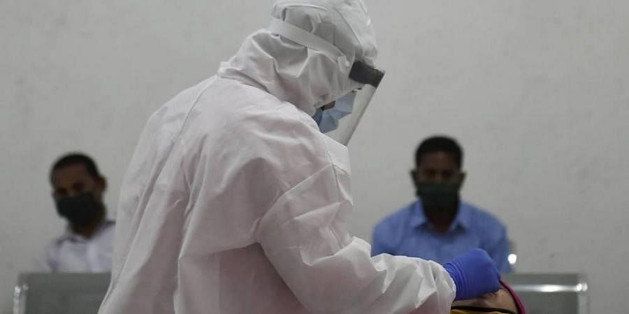 A health worker collects swab sample of a woman for Covid-19 testing at Dadar in Mumbai