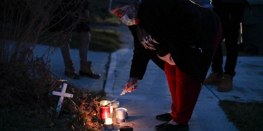 A neighbor lights a candle at a small memorial near the site of the fatal police shooting of Andre Hill
