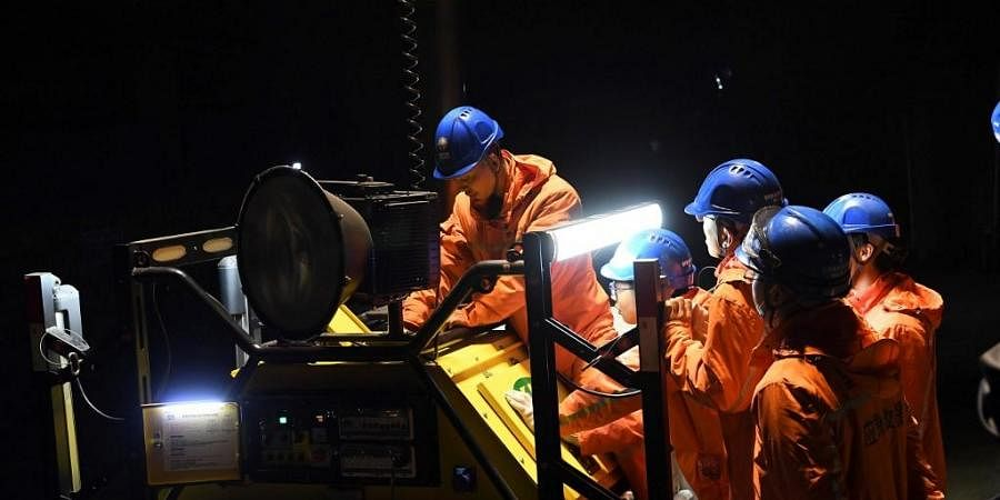 Rescuers adjust an emergency generator at the Diaoshuidong coal mine in southwestern China's Chongqing. (Photo | AFP)