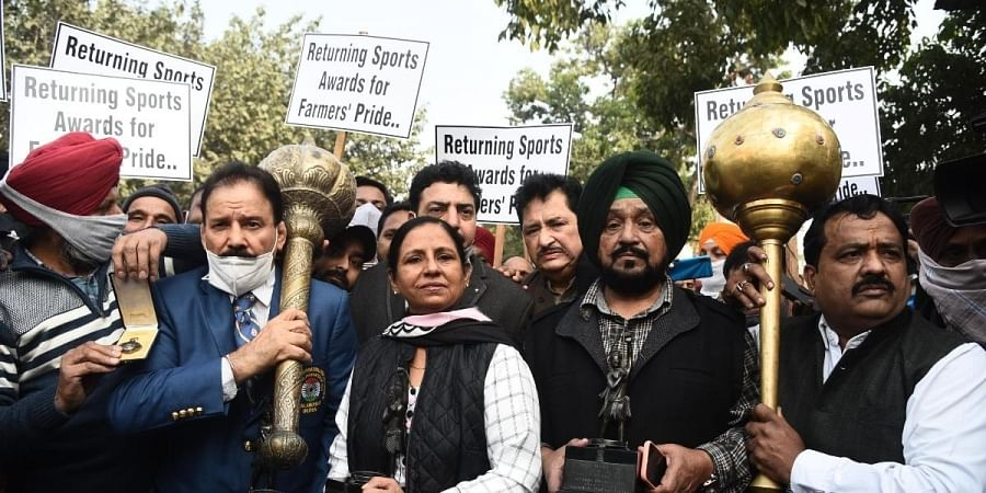 Wrestler Kartar Singh, hockey players Rajbir Kaur, Gurmail Singh and other sportspersons march towards Rashtrapati Bhavan to return their awards to the President in New Delhi.