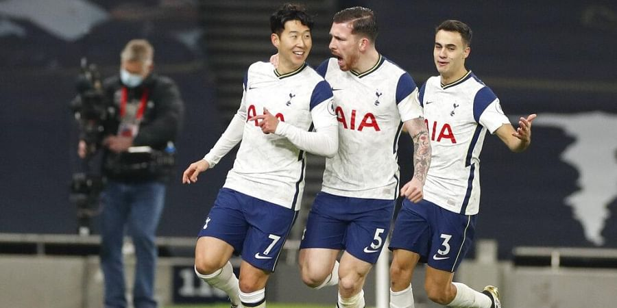 Tottenham's Sergio Reguilon, right, and Pierre-Emile Hojbjerg, center, celebrate with Son Heung-min, left, who scored his side's first goal against Arsenal.