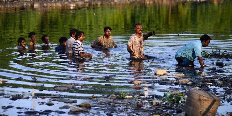 Slum dwellers standing neck-deep inside the polluted Cooum river as they protest against their eviction near Island Grounds in Chennai on Wednesday. (Photo   Debadatta Mallick, EPS)