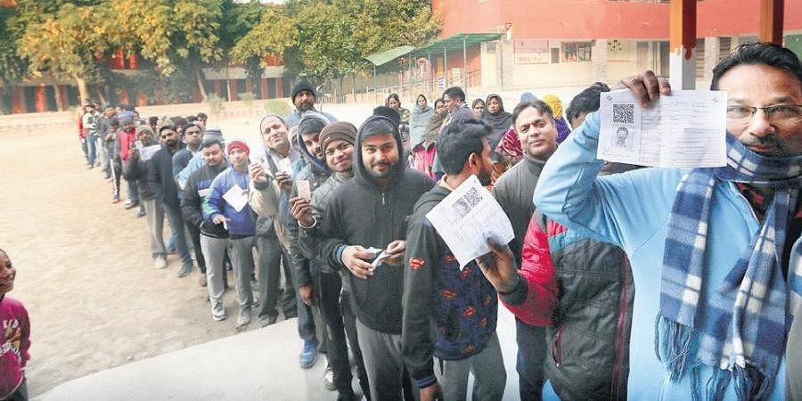 Voters stand in queue to cast their vote during the Delhi Assembly elections in New Delhi.