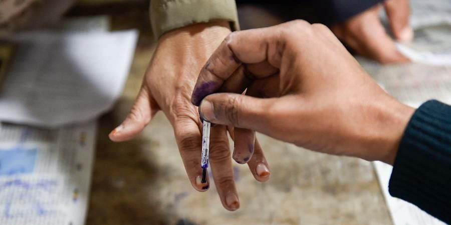 A polling official applies indelible ink on the finger of a voter during the Delhi Assembly elections at a polling station.