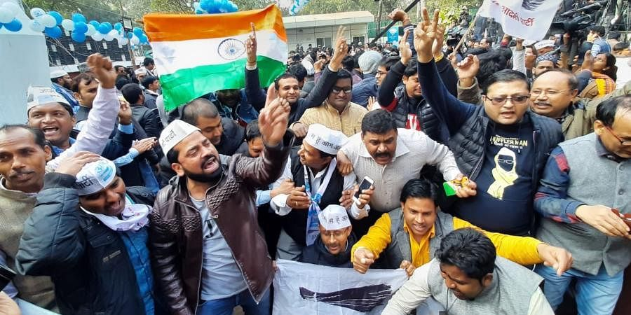 AAP workers celebrate at party office in New Delhi on Tuesday.