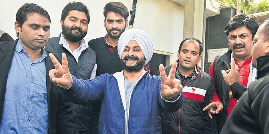 Newly-elected AAP MLA Jarnail Singh dances as he arrives for a meeting at the residence of party chief Arvind Kejriwal, in Delhi on Wednesday.