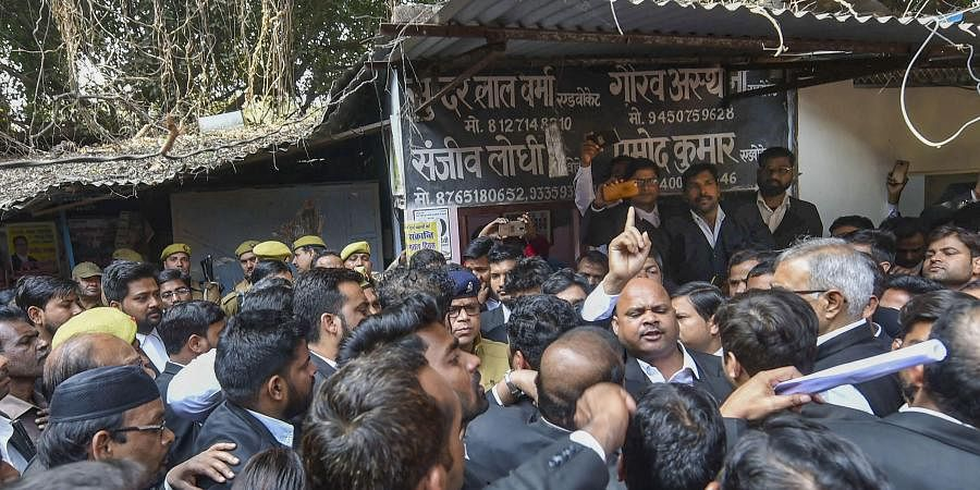 Sanjeev Lodhi, joint secretary of the Lucknow bar association, along with other lawyers raise slogans during a protest after a crude-bomb exploded in the premises of a court, in Lucknow, Thursday.