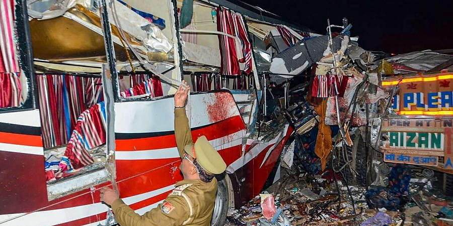 Policeman inspects the mangled remains of a private bus which collided with a truck on the Agra-Lucknow Expressway, in Firozabad.