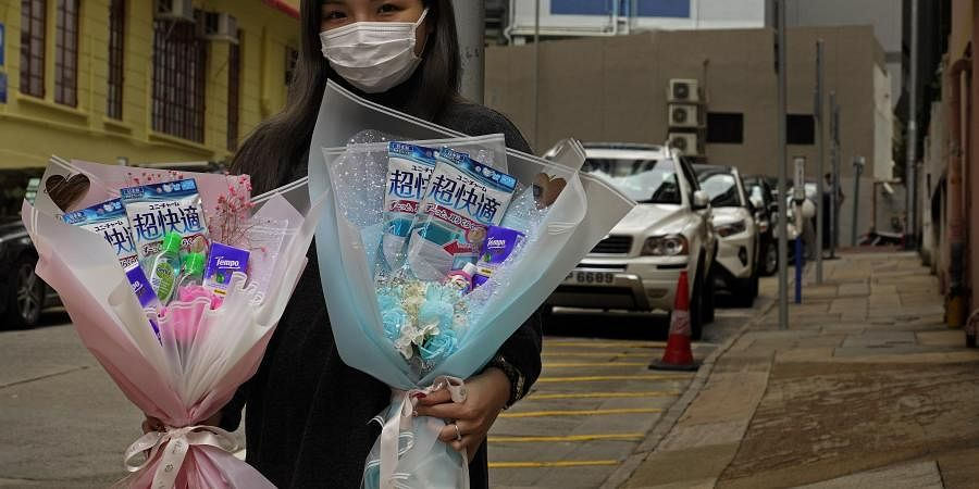 Flower shop owner Iris Leung wears her protective face mask as she delivers flowers with masks to customers on Valentine's Day in Hong Kong. (Photo | AP)