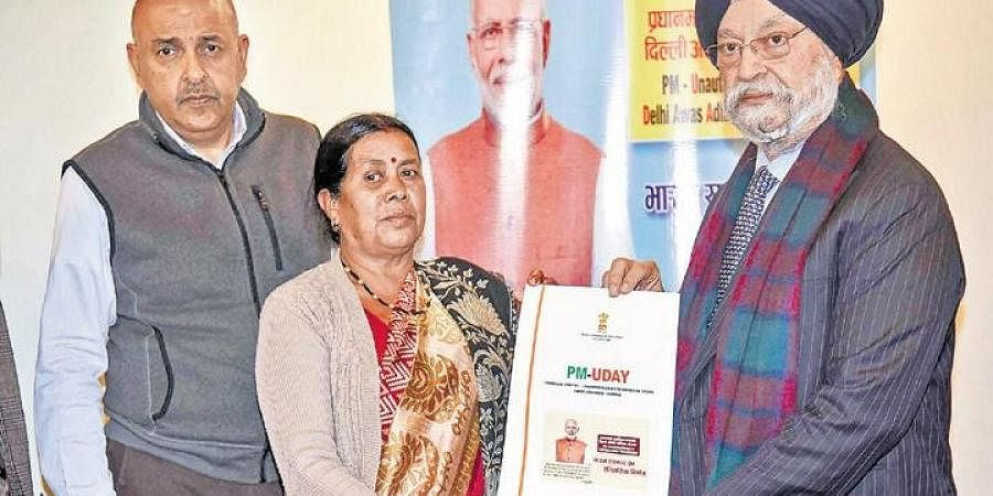 Minister of State for Housing & Urban Affairs Hardeep Singh Puri hands over the conveyance deeds and registry papers of houses to residents on Friday.