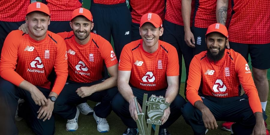 England's captain Eoin Morgan, second from right, with teammates pose for photographers after winning the T20 cricket series against South Africa at Centurion Park in Pretoria, South Africa, Sunday, Feb. 16, 2020.