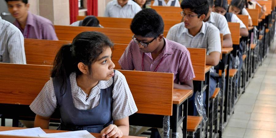 Students write their examination at an exam center.