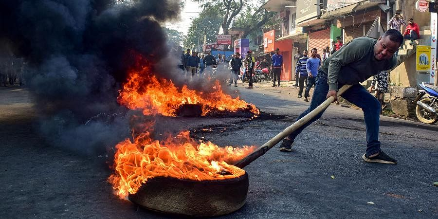 A demonstrator burns tyres on National Highway 17 during a protest rally against CAB at Boko in Kamrup district of Assam.
