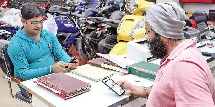 An automobile shop owner keeps track of the Budget 2020 in Bhubaneswar on Saturday