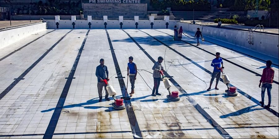 Workers clean tiles of Jayanagar swimming pool which will be inaugurated next month