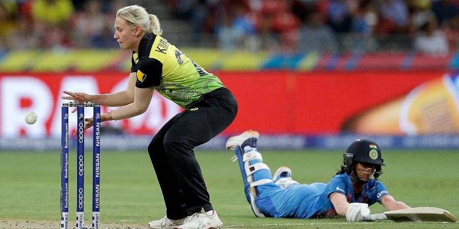 India's Jemimah Rodrigues, right, slides to make her ground as Australia's Delissa Kimmince attempts a runout during the first game of the Women's T20 Cricket World Cup in Sydney.