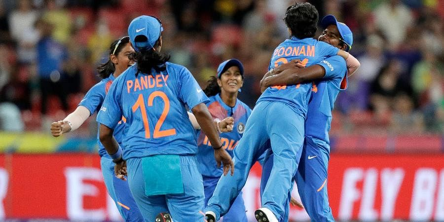 India's Poonam Yadav second right, is lifted by a teammate after taking the wicket of Australia's Ellyse Perry during the first game of the Women's T20 Cricket World Cup in Sydney.