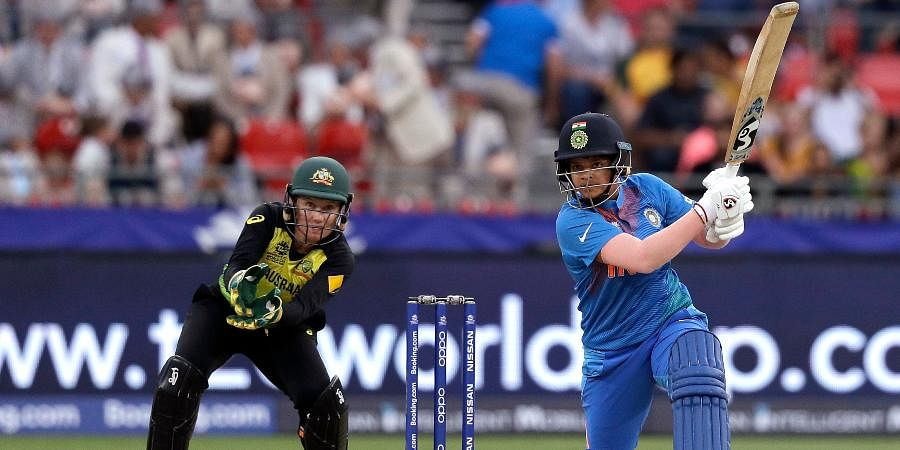India's Shafali Verma, right, drives the ball for 4 runs as Australia's Alyssa Healy watches during the first game of the Women's T20 Cricket World Cup in Sydney.