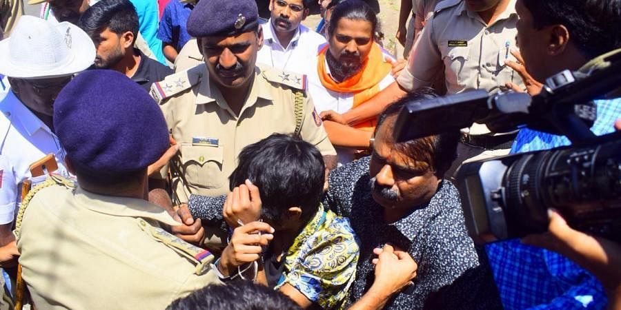 A girl sitting with a 'Kashmir Mukti, Dalit Mukti' placard arrested by police at the Town Hall, Bengaluru
