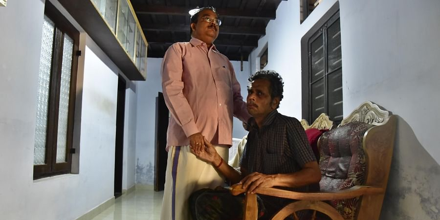 Justice P Somarajan consoles Gokulanatha Kaimal father of the deceased Gopika Gokulanathan at their residence on Thursday.
