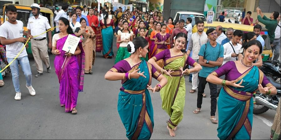 Artistes perform at the busy Sarakki junction