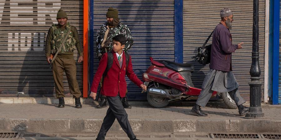 A Kashmiri schoolboy walks past soldiers outside his school in Srinagar