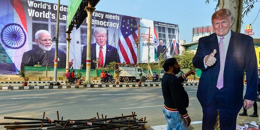 A worker arranges billboards of US President Donald Trump near Taj Mahal ahead of his maiden visit to India in Agra